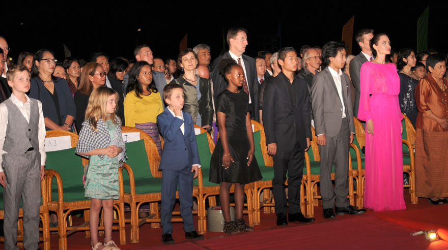 "Cambodian Minister of Culture and Fine Arts Phoeung Sackona (Front R), Hollywood star Angelina Jolie (2nd-R) and her children listen to Cambodian national anthem during the the premiere of Jolie's new film ""First They Killed My Father"" at the Elephant Terrace inside the Angkor park in Siem Reap on February 18, 2017. Angelina Jolie unveiled her new film on the horrors of the Khmer Rouge era on Saturday at the ancient Angkor Wat temple complex in Cambodia, a country the star shares a deep affinity with through her adopted son Maddox. / AFP / STR"
