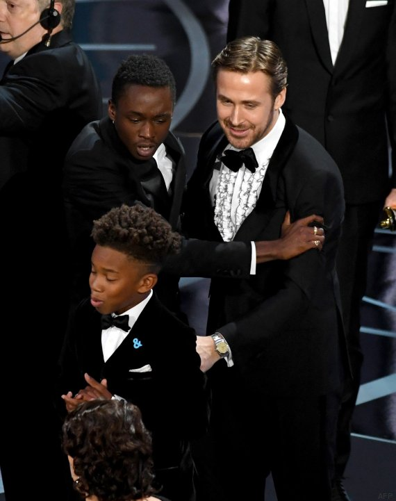 HOLLYWOOD, CA - FEBRUARY 26: Actor Ryan Gosling (R) congratulates actors Ashton Sanders (L) and Jaden Piner (C) after 'Moonlight' wins Best Picture onstage during the 89th Annual Academy Awards at Hollywood & Highland Center on February 26, 2017 in Hollywood, California. Kevin Winter/Getty Images/AFP == FOR NEWSPAPERS, INTERNET, TELCOS & TELEVISION USE ONLY ==