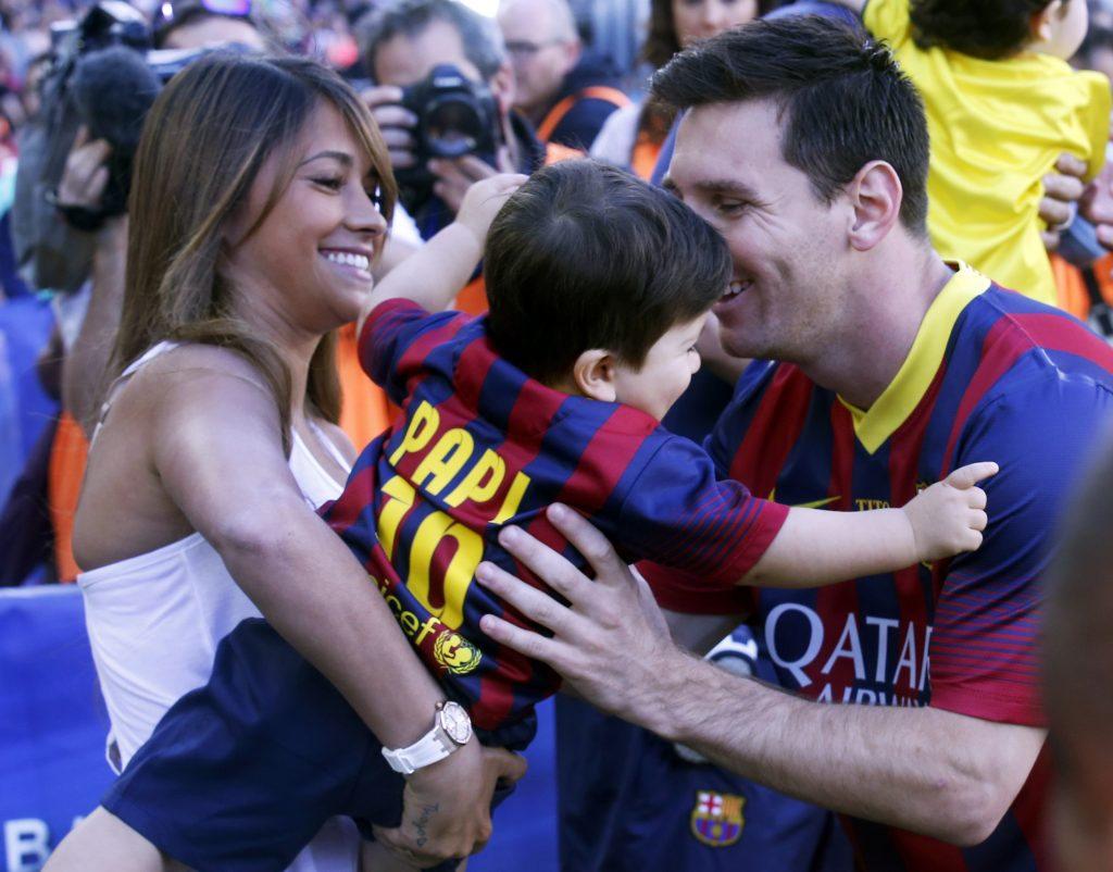 Barcelona's Lionel Messi (R) takes his soon Thiago from his partner Antonella Roccuzzo (L) before the La Liga soccer match against Getafe at Camp Nou stadium in Barcelona May 3, 2014. REUTERS/Albert Gea (SPAIN - Tags: SPORT SOCCER) - RTR3NNXW