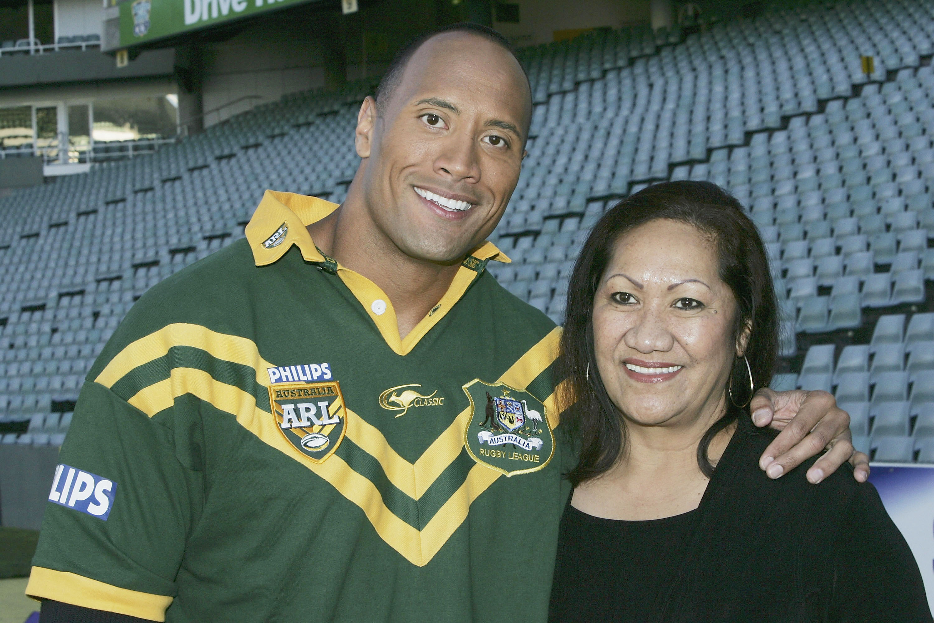 "SYDNEY, AUSTRALIA - AUGUST 5: Actor Dwayne ""The Rock"" Johnson poses with his mother Ata after receiving the Australian Rugby League official ""Kangaroo"" Jersey from a selection of national players at the Aussie Stadium on August 5, 2004 in Sydney, Australia. (Photo by Patrick Riviere/Getty Images)"