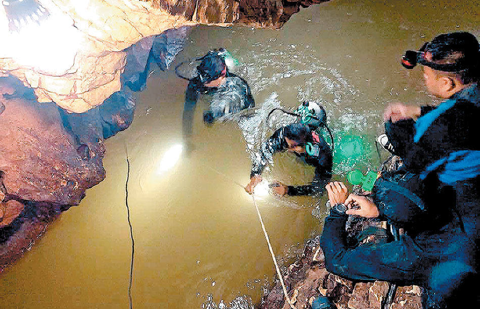 "This handout photo taken on June 28, 2018 and released by the Royal Thai Navy SEAL on June 29, 2018 shows a team of Royal Thai Navy SEAL divers inspecting the water-filled tunnel in the Tham Luang cave during a rescue operation for the missing children's football team and their coach in Chiang Rai province. A newly-discovered opening to a flooded Thai cave where 12 children and their football coach have been stuck for six days raised hopes for the massive rescue operation for survivors on June 29. / AFP PHOTO / AFP PHOTO AND ROYAL THAI NAVY SEAL / Handout / XGTY - RESTRICTED TO EDITORIAL USE - MANDATORY CREDIT ""AFP PHOTO / ROYAL THAI NAVY SEAL"" - NO MARKETING NO ADVERTISING CAMPAIGNS - DISTRIBUTED AS A SERVICE TO CLIENTS"